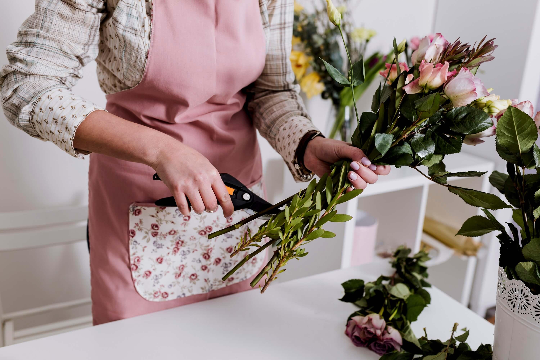 Blomsterforhandler står i blomsterbutik og laver buketter